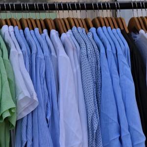 Un portant avec des vêtements dans les ton bleu et vert