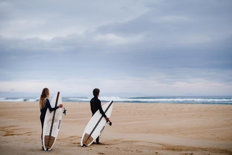Deux personnes faces à l'océan avec des surfs Nomads