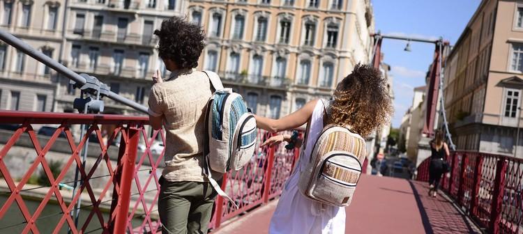 Deux personnes avec des sacs Himalayan Made sur un pont lyonnais